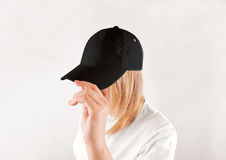 Blank black baseball cap mockup template, wear on women head. Isolated, side view. Woman in clear grey hat and t shirt uniform mock up holding visor of caps Stock Photos