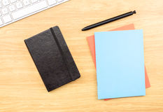 Blank Black,blue and orange notebook ,pen and keyboard on wooden Stock Image