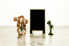 Blank black board with alarm clock and small palm tree on world map Stock Images