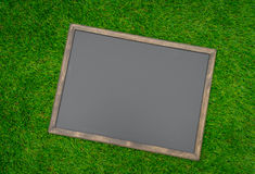 Blank black board on grass field. Stock Photos
