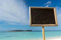 Blank black board on tropical beach background. Stock Photo