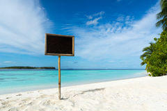Blank black board on tropical beach background. Blank black board on tropical beach background Royalty Free Stock Image