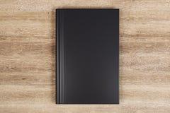 Blank black book. Blank closed black hardcover book on wooden desktop background. Close up. Publish and info concept. Mock up, 3D Rendering stock illustration