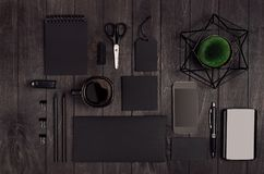 Blank black business stationery set with phone, coffee cup, green plant on dark elegant wood table. Modern fashion simple work place Royalty Free Stock Photo