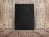 Blank black canvas poster leaning at wood wall on wooden floor i Royalty Free Stock Image