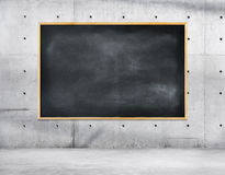 Blank Black Chalkboard on a Concrete Wall Stock Photo