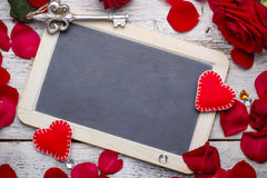 Blank black chalkboard. With petals and handmade hearts Royalty Free Stock Image