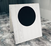 Blank black circle on white wooden chalkboard on concrete floor,. Mock up Royalty Free Stock Photos
