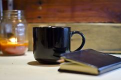Blank black coffee mug morning journal. A blank black coffee mug and a candle in a mason jar on a wooden work bench table getting ready for work writing down the stock photos