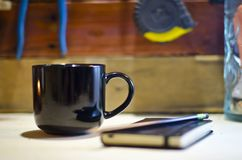 Blank black coffee mug tool table journal. A blank black coffee mug and a candle in a mason jar on a wooden tool bench table getting ready for work writing down royalty free stock photo
