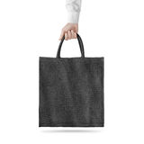 Blank black cotton eco bag design mockup isolated, holding hand Stock Image