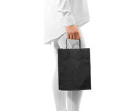 Blank black craft textured paper bag mockup holding hand Royalty Free Stock Photo