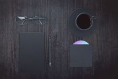 Blank black diary cover with cup of coffee, eyeglasses and CD di Royalty Free Stock Image