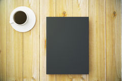 Blank black diary cover with cup of coffee on wooden table Royalty Free Stock Photography