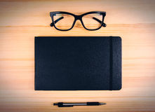 Blank black diary with eyeglasses and pen on wooden table, mock Royalty Free Stock Photos