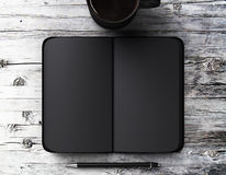 Blank black diary with pen and a cup of coffee on a wooden table Royalty Free Stock Photos