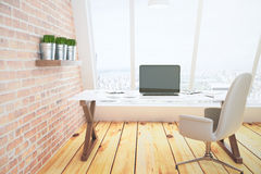 Blank black laptop screen on glassy table in loft room with bric Royalty Free Stock Image