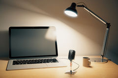 Blank black laptop screen, vintage radio microphone and lamp on Stock Photography