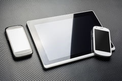 Blank Black Mobile Lying Next To A Business Tablet With Reflection And A White Smartphone On It's Corner, All Above A Carbon Layer Stock Image