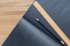 Blank black notebook with black pencil and ruler Stock Photography