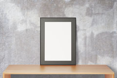 Blank black picture frame on wooden table and concrete wall, moc Stock Photos