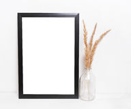 Blank black picture frames , Mockup in hipster style workspace. Blank black picture frames on on  white background ,with the decor of dry twigs and glass vases Royalty Free Stock Images