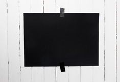 Blank black poster hanging on a tape on white wooden plank wall. Stock Photos