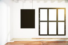 Blank black poster on white wall in empty loft room  Royalty Free Stock Photos