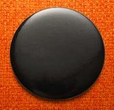 Blank black round badge. Blank single black round badge in closeup stock photography
