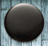 Blank black round badge on wood. En background stock image