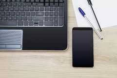 Blank black screen smartphone beside laptop with paper and pens on wooden desk. Business concept Stock Photos