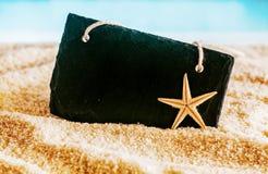 Blank black sign on golden sea sand Stock Photos