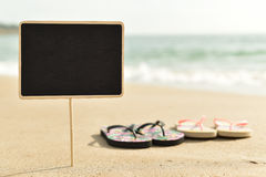 Blank black signboard on the beach. Closeup of a blank black signboard and two pairs of flip-flops on the sand of a beach Stock Photos