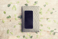 Blank black smartphone with diary on wooden table with leaves Stock Photos