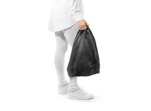 Blank black t-shirt plastic bag mockup holding hand. Woman hold space carrier sac mock up. Disposable bagful branding template. Shopping carry package in Royalty Free Stock Photo