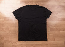 Blank black t-shirt on a wooden surface Royalty Free Stock Image