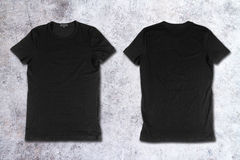 Blank black t-shirts on a concrete surface Stock Image