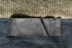 Blank clothes label. Blank black textile clothes label on knitted background closeup royalty free stock photos