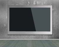 Blank black wide flat TV screen hanging on wall. Blank black wide flat TV screen hanging on concrete wall Royalty Free Stock Photos