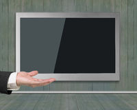 Blank black wide flat TV screen hanging on wooden wall Royalty Free Stock Photos
