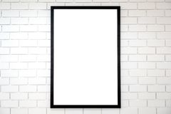 Blank black wooden picture frame on white brick wall background stock photography