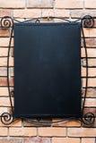 Blank blackboard at a brick wall Stock Photo