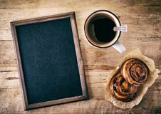 Blank blackboard. With buns and cup of coffee on wooden background Royalty Free Stock Photography