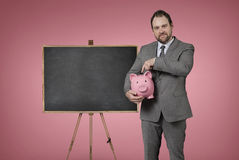 Blank blackboard with businessman holding piggy bank at office Royalty Free Stock Photo