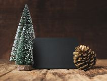 Blank blackboard with christmas tree and gold pine cone and snow falling on grunge wood table and dark brown wooden wall.winter stock image