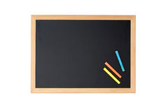Blank blackboard with colored chalks Royalty Free Stock Photography