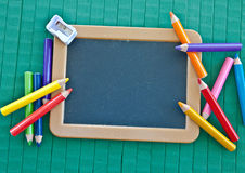 Blank blackboard and colorful crayons Stock Photos