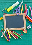 Blank blackboard and colorful office utensils Stock Images