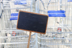 Blank blackboard and empty shopping carts in the background. For your text Stock Images