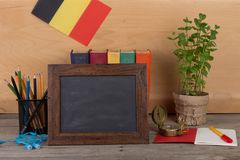 Blank blackboard, flag of the Belgium, books, chancellery on table and wooden background. Education concept - blank blackboard, flag of the Belgium, books stock images